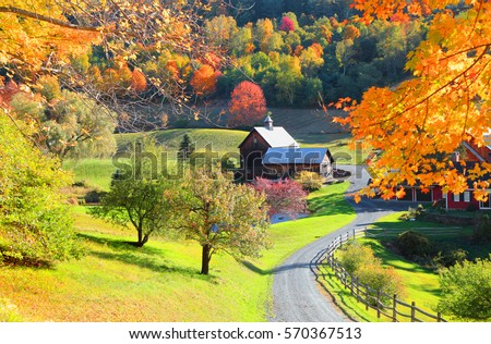 Barn in Vermont country side surrounded by autumn trees\n
