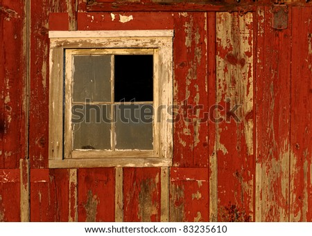 Barn window on bright red textured wall