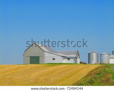 Barn with silos in open field and blue sky