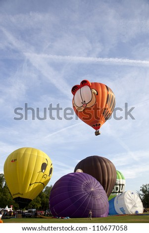 BARNEVELD, THE NETHERLANDS - AUGUST 17: Colorful Garfield and other air balloons taking off at international balloon festival Ballonfiesta on August 17, 2012 in Barneveld, The Netherlands - stock photo
