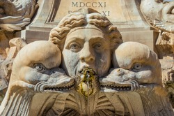 Baroque art in Rome. Marble mask among dolphins or fish from 18th century Fountain of the Pantheon