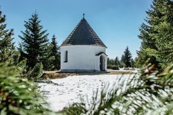 Baroque Chapel of the Visitation of the Virgin Mary (Kunstat Chapel) located in Eagle Mountains at altitude of 1035 m, Czech Republic.Circular floor plan and roof covered with shingles.Sunny day