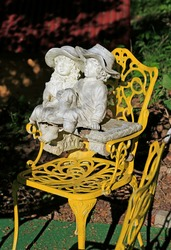 Baroque or rococo garden design: Garden sculpture of a dreamy young couple with hats sitting in intimate togetherness on a yellow iron garden chair blurred background