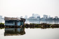 Barrack at lake in Hanoi against skyline of skyscrapers