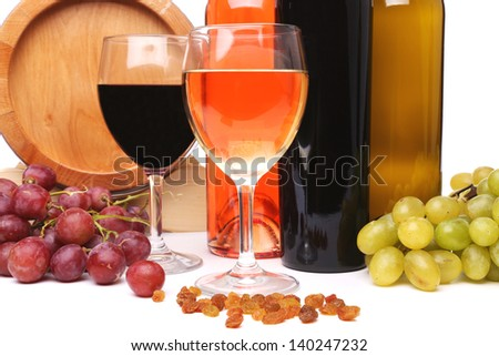 barrel, bottles and glasses of wine and ripe grapes on wooden