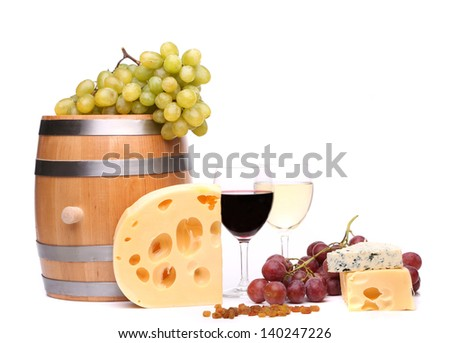 barrel, cheeses, glasses of wine and ripe grapes on wooden