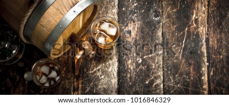 barrel of Scotch whiskey with a glass. On a wooden background. #1016846329