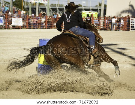 Barrel racing competition at the local rodeo - stock photo
