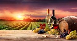 Barrel Wineglasses And Bottle In Vineyard At Sunset