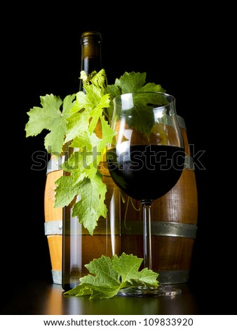 Barrels of wine bottles and glasses, decorated with vine leaves.
