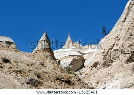 Barren and dry, Tent Rocks State Park has unusual rock formations carved by wind and erosion.  Vivid blue sky and white sun bleached mountains.