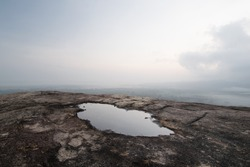 Barren rock and puddle. Panorama shot of the sunrise sky and its reflection in a puddle of water, from the vantage point of Pidurangala rock, next to the famous Sigiriya Lion Rock in Sri Lanka.