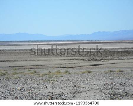 Barren rocky desert landscape with hazy mountains beyond under hazy blue sky.