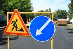 Barricade with traffic signs on city street. Road repair