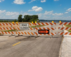 Barricades and signs warn of a road being closed due to flooding along the Mississippi River