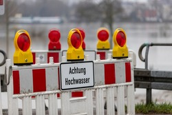 barrier blocking a way to the edge of rhine river, sign with german letters meaning caution high water, flood