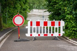Barriers on a road with barricade and no through sign. Road not passable due to flooding of the river in the background.