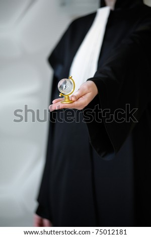 Barrister in wig holding a glass globe in her hand. Great file for your legal brochure, global business flyer or site.