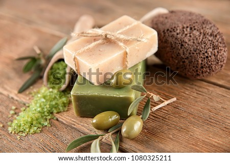 Bars of natural soap with olive extract on table