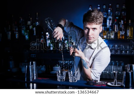 Bartender bartender is pouring a drink and looking at the camera