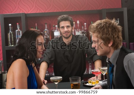 Bartender behind the bar couple having chat and drink