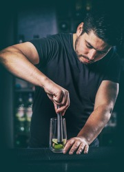 Bartender crushed with a muddler lime for mojito cocktail