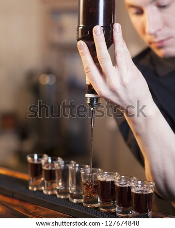 bartender fills a few glasses in a row at the same time
