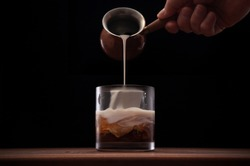 Bartender finishing a White Russian cocktail by topping the drink with cream on a dark background