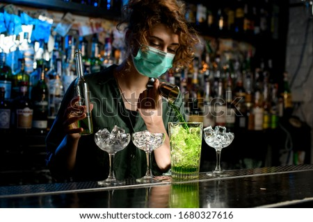 bartender girl actively pour green liquid from beaker into glass with ice. Medical mask for prophylaxis and protection from coronavirus COVID-19.