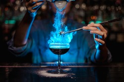 Bartender girl adding to a brown cocktail and pour on a flamed badian on tweezers a powdered sugar on the bar counter in the blue light.