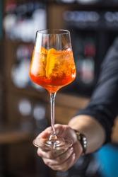 Bartender hand holding glass with  Aperol Spritz drink.