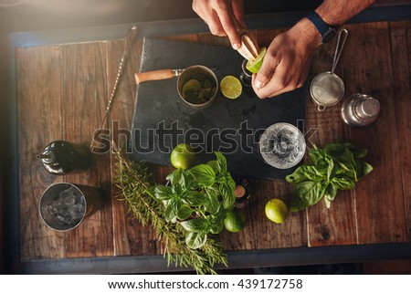 Bartender hands juicing lemon with a reamer. Bartender experimenting with creating new cocktails ideas. Cocktail accessories with lemons, basil and lavender on table.