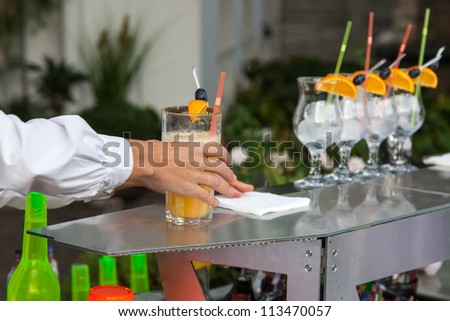 Bartender holds glass of cocktail outdoors