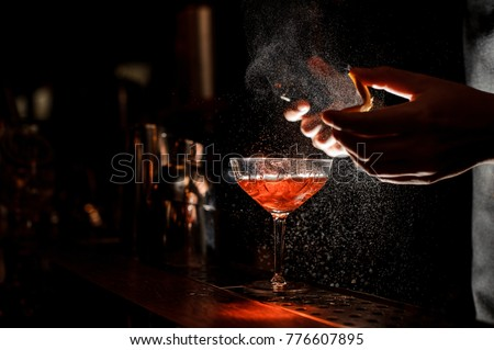 Photo of Bartender in black apron and blue shirt sprays an orange peel in cocktail glass with ice at a bar counter