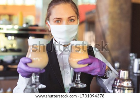 bartender in medical mask and gloves makes latte coffee