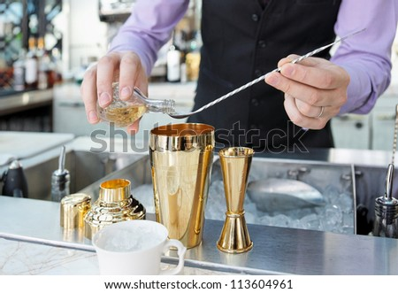 Bartender is adding ingredient in shaker at bar counter