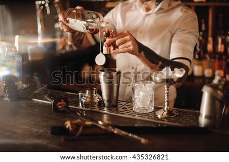 bartender is adding ingredient...