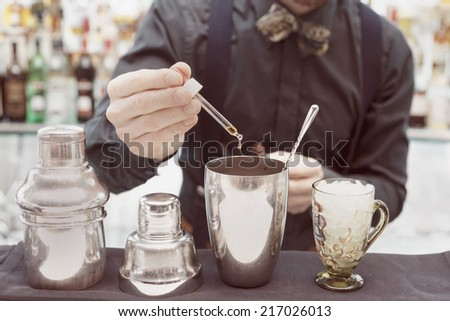 Bartender is making cocktail at bar counter, adding some bitter in the shaker, toned image