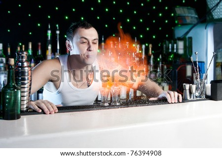 bartender is making flaming cocktail with performance