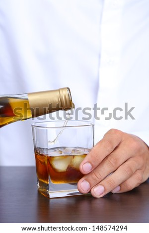 Bartender is pouring whiskey into glass