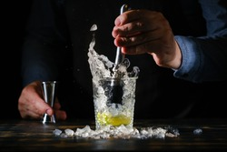 Bartender is preparing a refreshing cocktail with ice and lime. Bartender preparing Caipirinha cocktail. Summer cocktail at the nightclub.