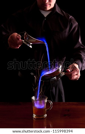 bartender making a flaming coffee drink with bright blue flames in a dark bar