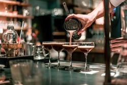 Bartender making alcoholic cocktail, summer cocktail in bar