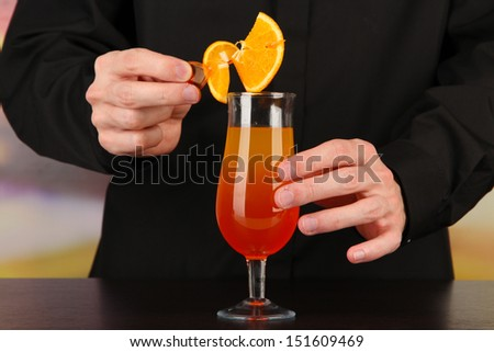 Bartender making and decorating cocktail on bright background, close-up