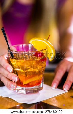 Bartender making new old fashioned cocktail in Italian restaurant.