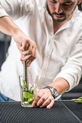 Bartender mashed with a muddler mint leaf and lime for mojito cocktail