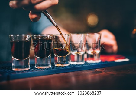 Bartender pouring and serving alcoholic drinks at bar  #1023868237