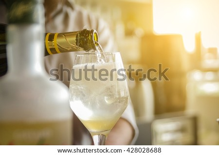 Bartender pouring champagne into glass - close up - Concept about drink, alcohol and restaurant service