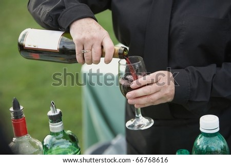 Bartender pouring glass of red wine from bottle