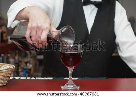 Bartender pouring glass of red wine from decanter